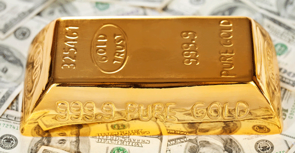 gold bar sitting on dollars